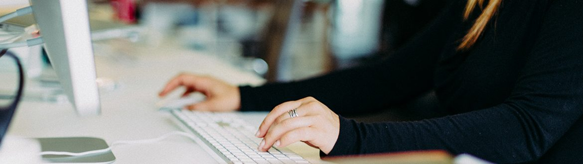 Woman typing on computer keyboard and holding mouse