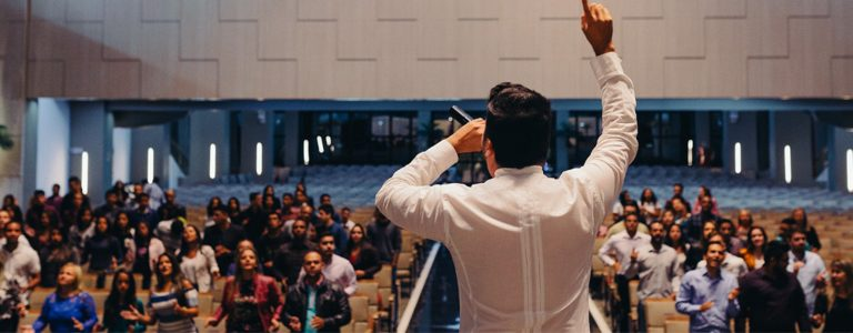 Pastor with hand raised preaching to congregation